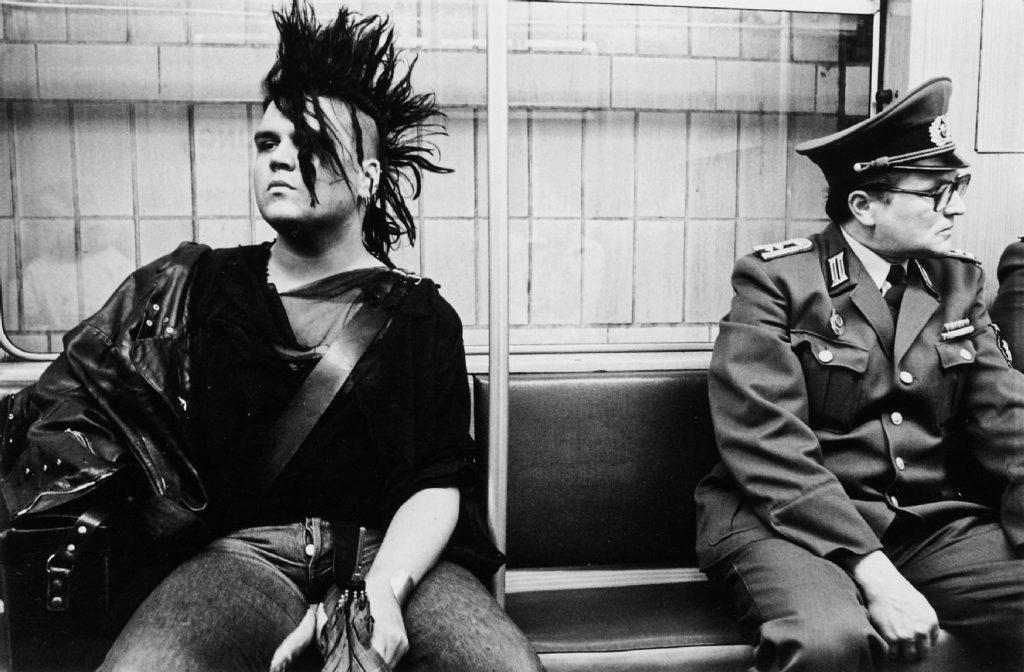 East German punk taking the U-Bahn next to an Volkspolizei officer, East Berlin, East Germany (1986)